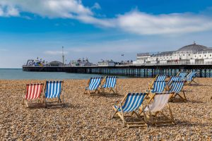 Brighton beach chairs and pier in background