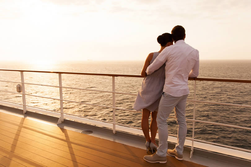 Couple on cruise ship deck watching sunset