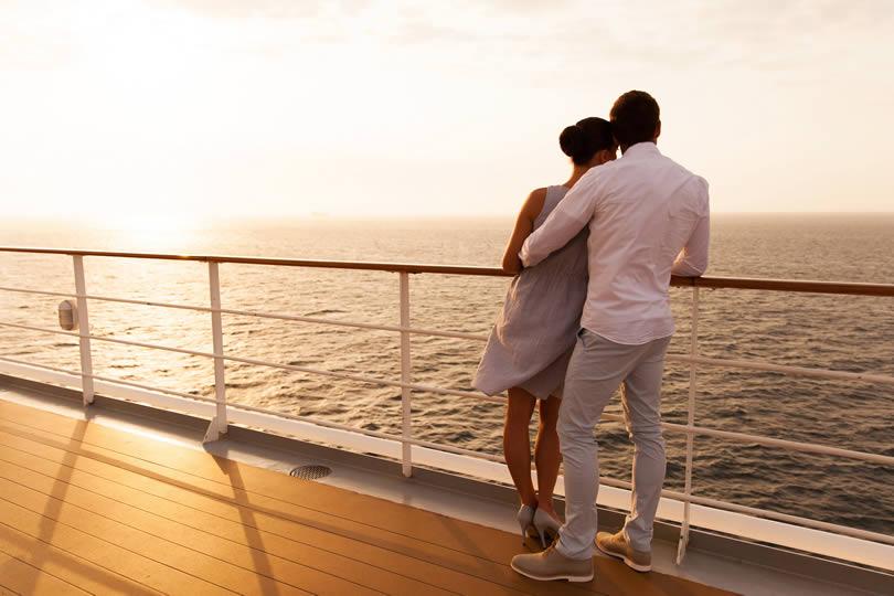 Couple on cruise ship deck watching sunset